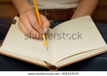 Girl in blue jeans with massive belt sitting on the floor in lotus pose and going to write something in her notebook by pencil - stock photo
