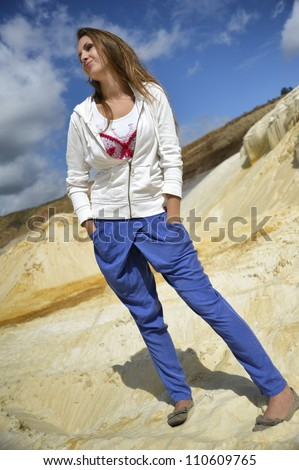 girl in blue pants and a white jacket on the bright sand - stock photo