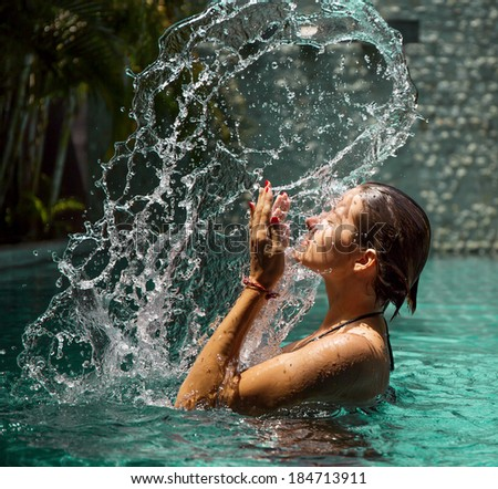 Girl in blue swimming pool with splash and drops - stock photo