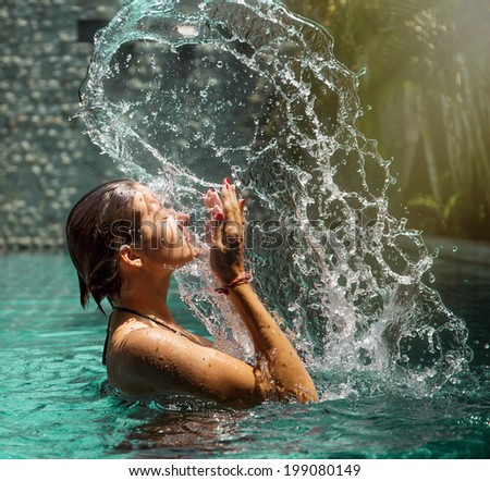 Girl in blue swimming pool with splash and drops