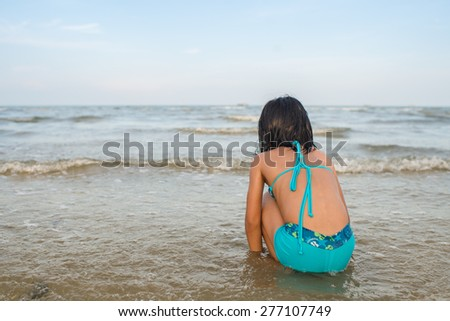 Girl in blue swimsuit  enjoying the beach. - stock photo