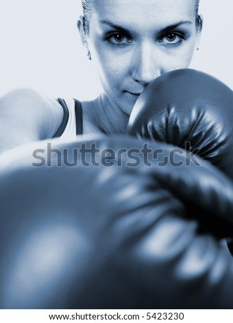 Girl in boxing gloves (toned in blue) - stock photo