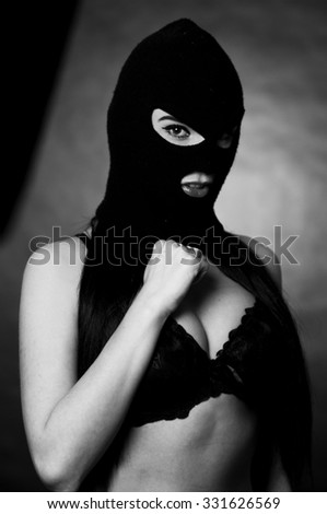 girl in bra and balaclava - black and white photo in studio of a psycho girl terrorist - stock photo
