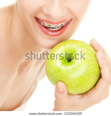 Girl in braces with green apple on white background - stock photo