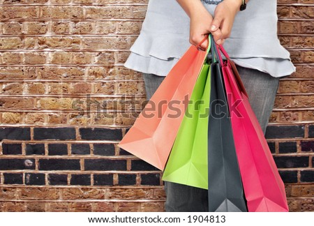 girl in bright colours holding shopping bags over a brick wall - stock photo