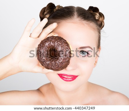 girl in bright makeup eating a tasty donut with icing. Funny joyful woman with sweets, dessert. dieting concept. junk food - stock photo