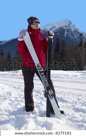 Girl in bright ski clothes with white skis  on a mountain background