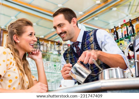 Girl in cafe or coffee bar flirting with barista who is busy preparing Cappuccino with professional machine - stock photo
