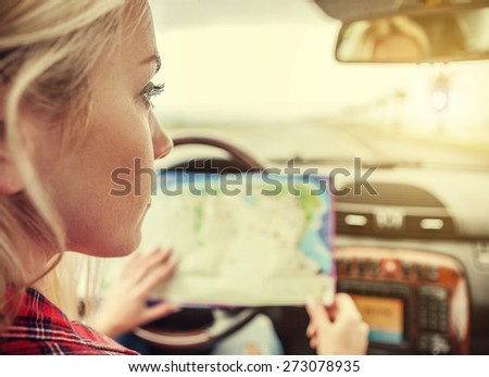 Girl in car with roads map - stock photo