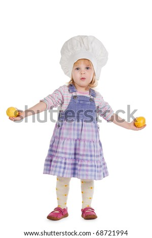 Girl in chef hat with lemons in their hands - stock photo