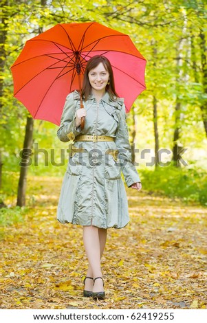 girl in cloak with umbrella in autumn park - stock photo