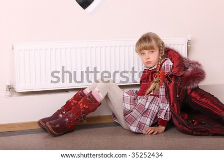 Girl in coat warm  near radiator.  Energy crisis. - stock photo