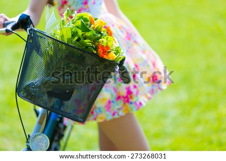 Girl in color short dress stands near bike with basket and flower bouquet - stock photo