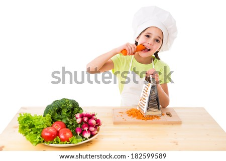 Girl in cooking hat eating the carrots, isolated on white - stock photo
