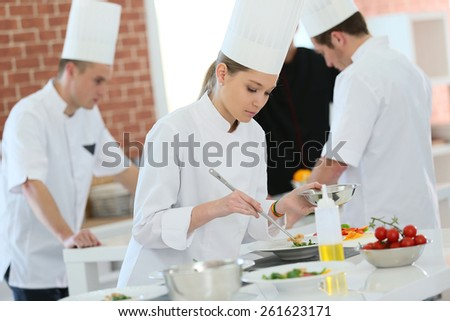 Girl in cooking training class preparing dish - stock photo