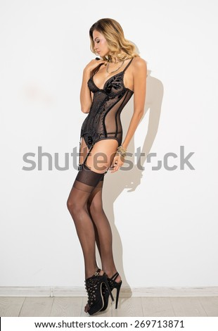 Girl in corset and lingerie posing against a white wall  - stock photo