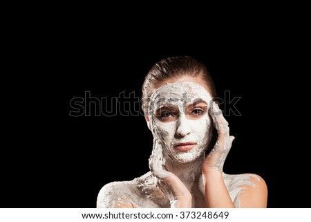 Girl in cosmetic mask on a black background
