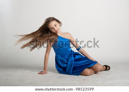 Girl in deep blue dress sitting with fluttering long hair - stock photo