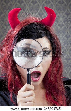 Girl in devil costume saw something unexpected against vintage wallpaper background. - stock photo
