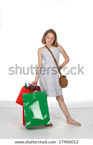 girl in dress holding her red and green Christmas shopping bags