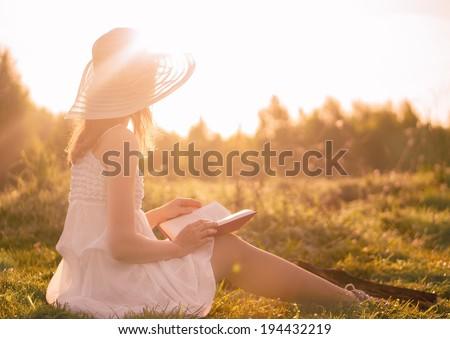 Girl in dress reading book. Sunny morning. - stock photo