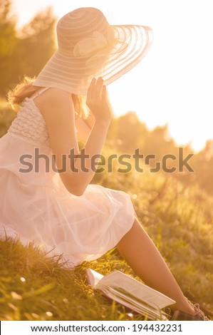 Girl in dress sitting at grass. Sunny morning.