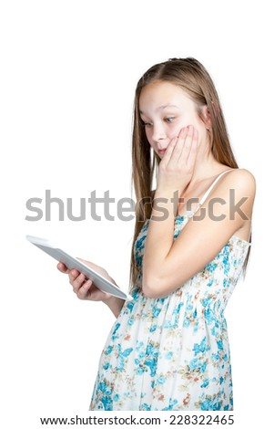 Girl in dress standing holding a tablet in her hand and is very surprised isolated on white background - stock photo