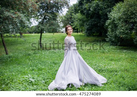 Girl in elegant dress walking and dancing on the beautiful meadow, the dress is flowing and flying. Natural background, outoors.