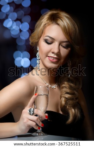 girl in evening dress at the bar with a glass of champagne over holidays lights boke background