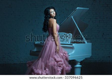 Girl in evening dress standing next to a large white grand piano. - stock photo