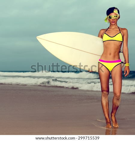 Girl in fashionable Swimwear standing on the beach with Surf board. - stock photo