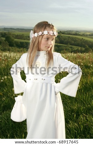 girl in first holy communion on landscape - stock photo
