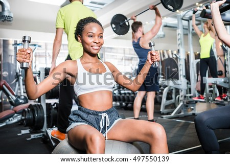 Girl in fitness gym exercising her shoulder on machine
