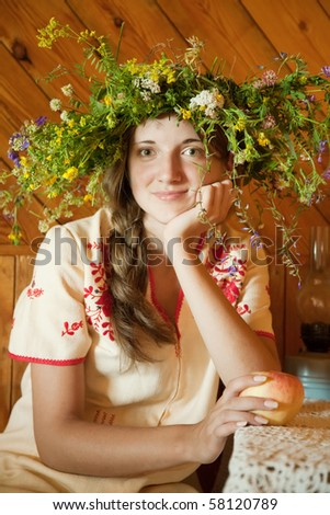 Girl in  flowers chaplet in wooden interior