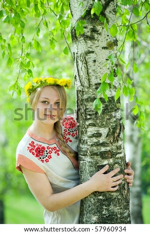 girl in flowers wreath and traditional clothes near birch - stock photo