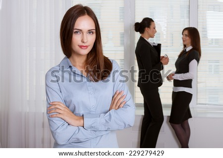Girl in formal clothes is standing in the foreground and her colleagues have a talking in the background - stock photo