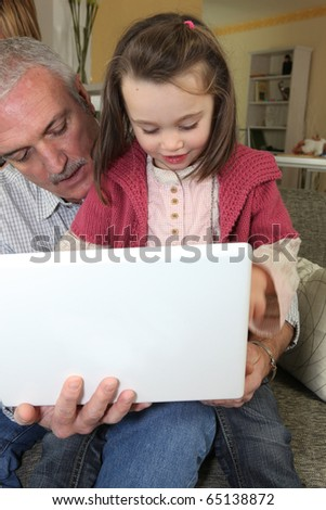 Girl in front of a computer with a senior man - stock photo