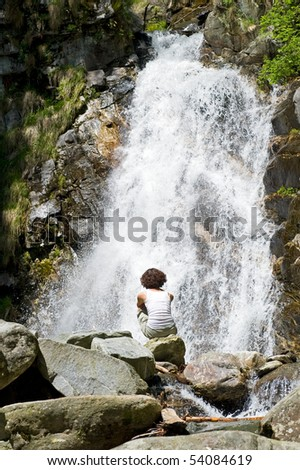 Girl in front of a waterfall. - stock photo