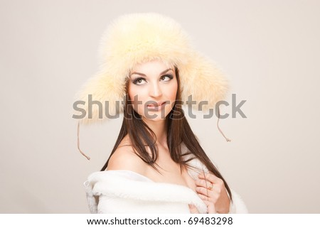 Girl in furry hat looking up, isolated studio shot