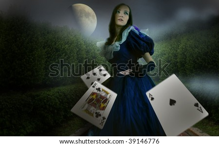 girl in garden with playing cards in the night - stock photo