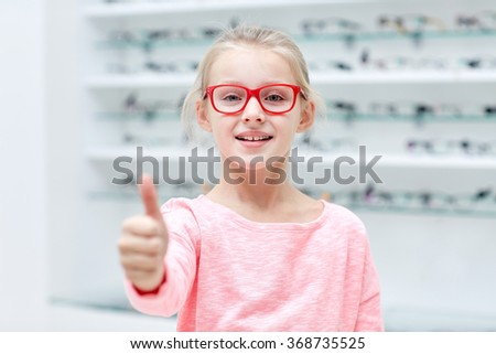 girl in glasses at optics store showing thumbs up - stock photo