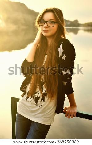 Girl in glasses at the river  - stock photo