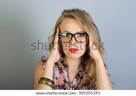 Girl in glasses full of doubts and hesitation. Girl is thinking. - stock photo