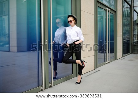 girl in glasses on a background of glass building