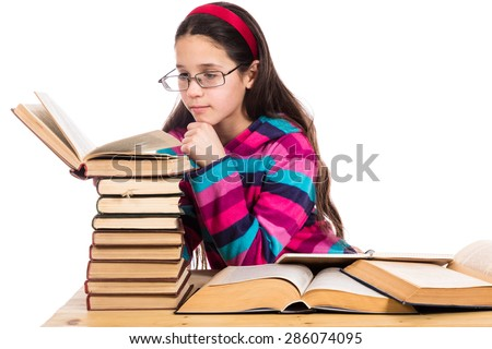 Girl in glasses reading the old book with pile of books, isolated on white - stock photo