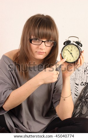 Girl in glasses with an alarm clock in her hand shows the time - stock photo
