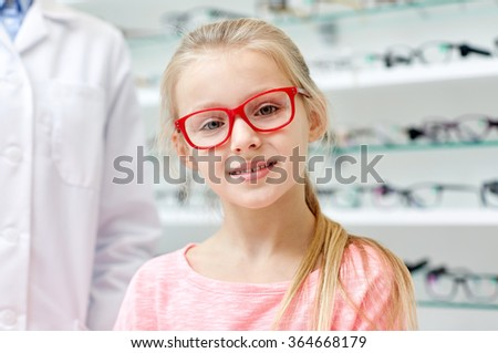 girl in glasses with optician at optics store - stock photo