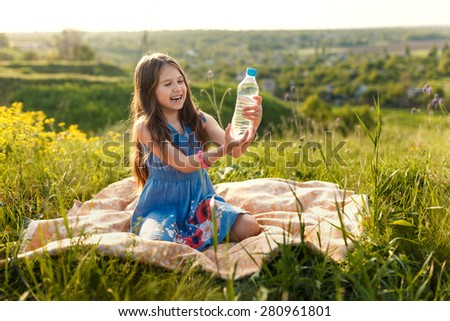 girl in grass with plastic bottle with water shows gesture by finger - stock photo