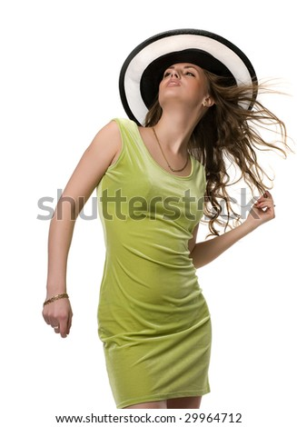 Girl in green dress and in a black hat hold in hand flying hairs and look upstairs, isolated on white - stock photo