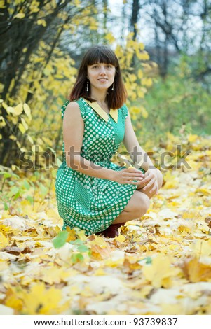 Girl in green dress at autumn park - stock photo